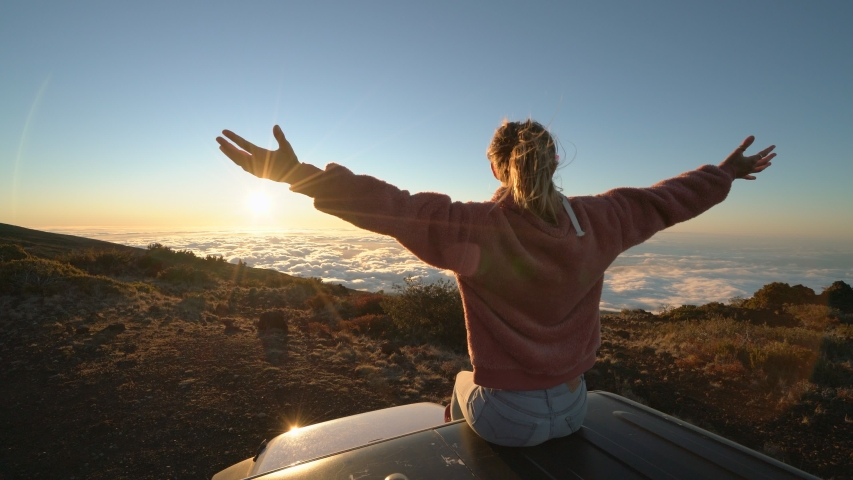 Woman sitting on top of car roof contemplating nature arms wide open looking at amazing sun rising above the clouds.  #1042902640