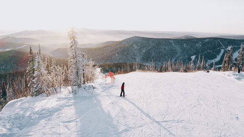 Skier in a red jacket on a snowy ski slope among the forest at sunset