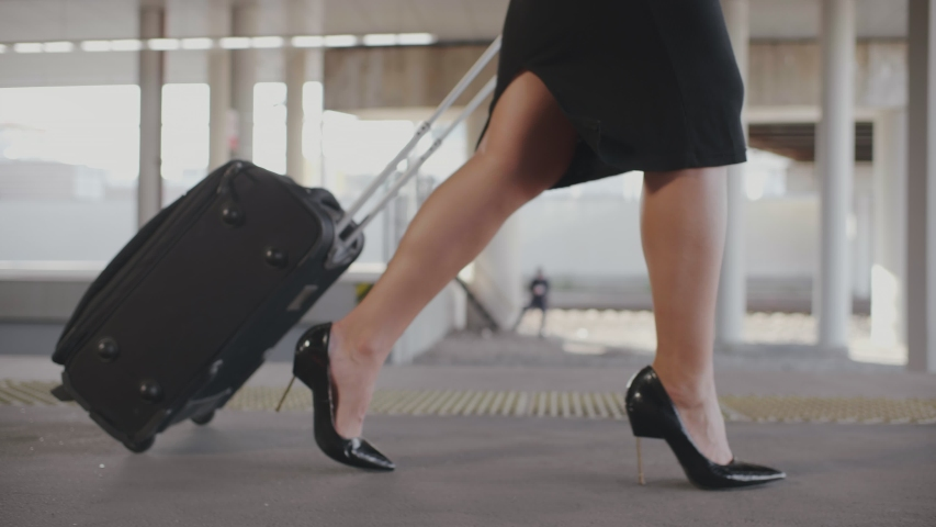 Black travel bag or suitcase on wheels in hand and female legs in black skirt and high heels shoes on feet walking along railway platform. Businesswoman office worker going on business trip by train Royalty-Free Stock Footage #1042920838