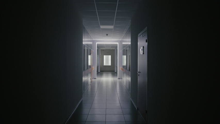 Tracking inside a long dark gloomy corridor of abandoned business center with offices or hospital at night. Concept of tunnel or horror. Leaved place