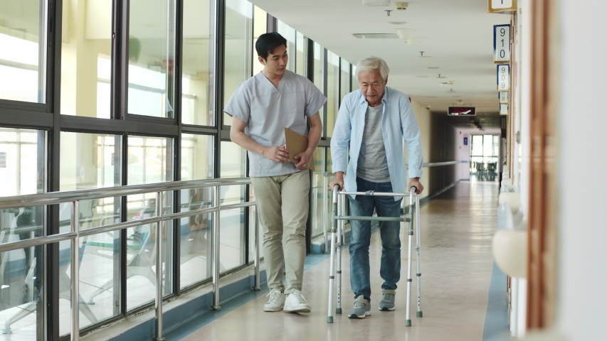 young asian physical therapist working with senior man on walking using a walker in rehab center or nursing home Royalty-Free Stock Footage #1042933408