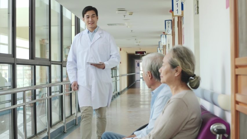 Young asian doctor telling senior couple test result in hospital corridors