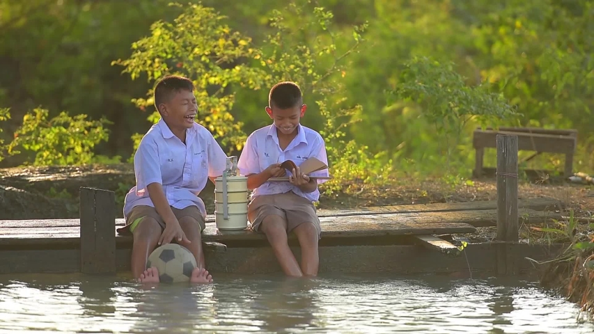 Asian student reading book with school uniform with football and Food carrier on the wood bridge in the rice fields  countryside Thailand country. Rural concept. | Shutterstock HD Video #1042936516