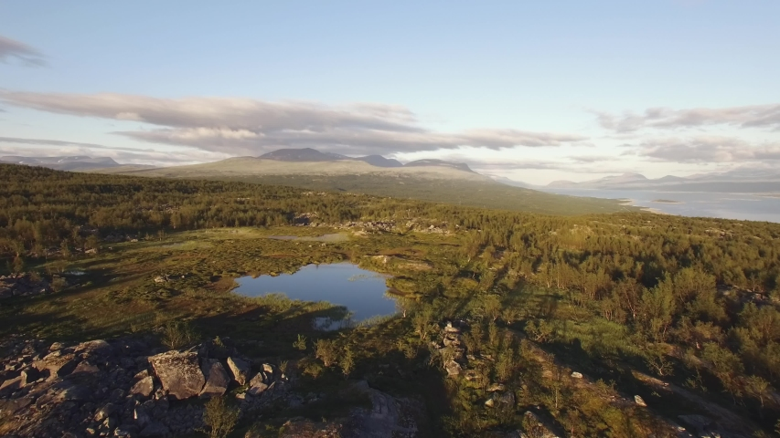 Aerial view of an arctic summer landscape in northern Scandinavia. Location: Ritsem, Sweden (Swedish Lapland). July of 2018.  Royalty-Free Stock Footage #1042940206