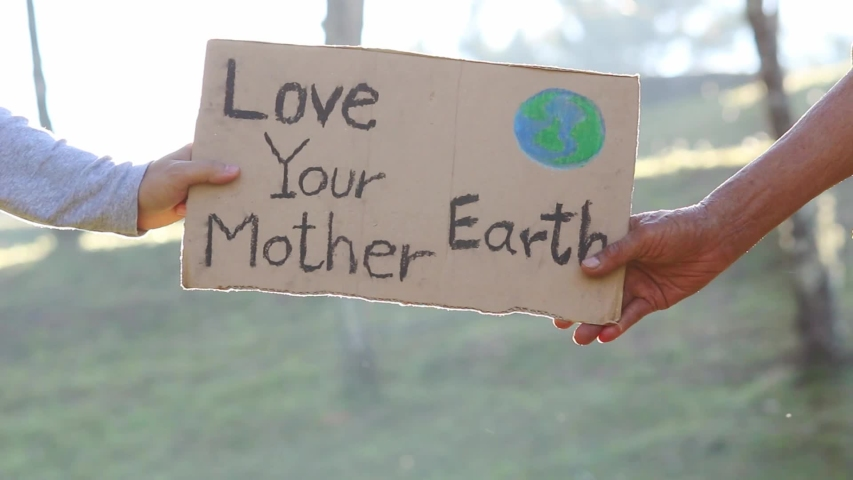 """Hands holding """"Love your Mother Earth"""" Poster on a demonstration due to climate change by plastic pollution. People standing in the park with a sign to save the world. 