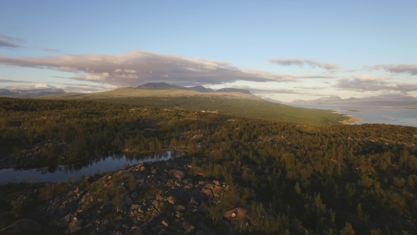 Flying over a beautiful arctic landscape in northern Scandinavia. Location: Ritsem, Sweden (Swedish Lapland). July of 2018.  Royalty-Free Stock Footage #1042940746