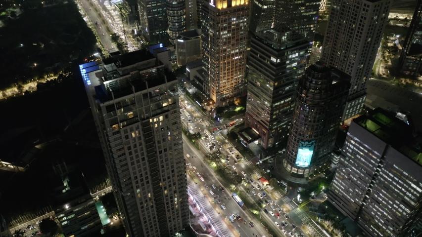 Futuristic skyscraper Jakarta cityscape aerial view high above night illuminated business towers capital city traffic below. Sudirman. Senayan | Shutterstock HD Video #1042947298
