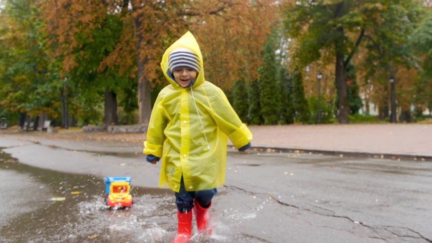 4k slow motion footage of happy smiling little boy pulling toy truck and running over puddles at autumn park after rain