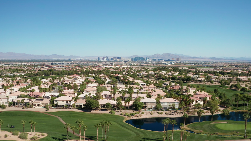 Aerial dolly shot of Las Vegas suburban homes, golf course with city skyline | Shutterstock HD Video #1042963216