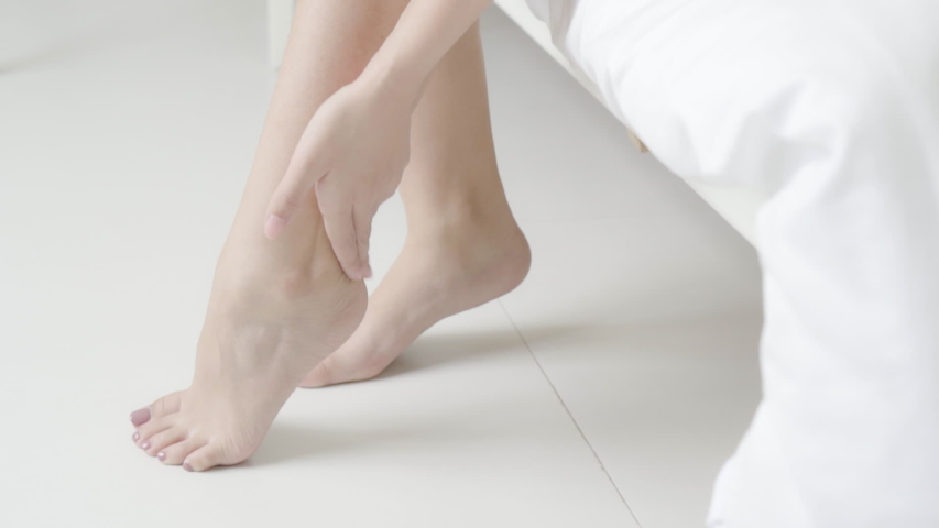 Closeup beautiful young asian woman applying cream and lotion touch foot dry on bed, beauty asia girl moisturizer and treatment cosmetic on to toes and heel, skincare cosmetic and healthy concept.