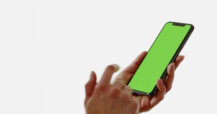 MINSK/BELARUS - CIRCA 2019: GREEN SCREEN CU Caucasian female using iPhone XS Max against white background, vertical orientation. 4K UHD RAW Graded footage