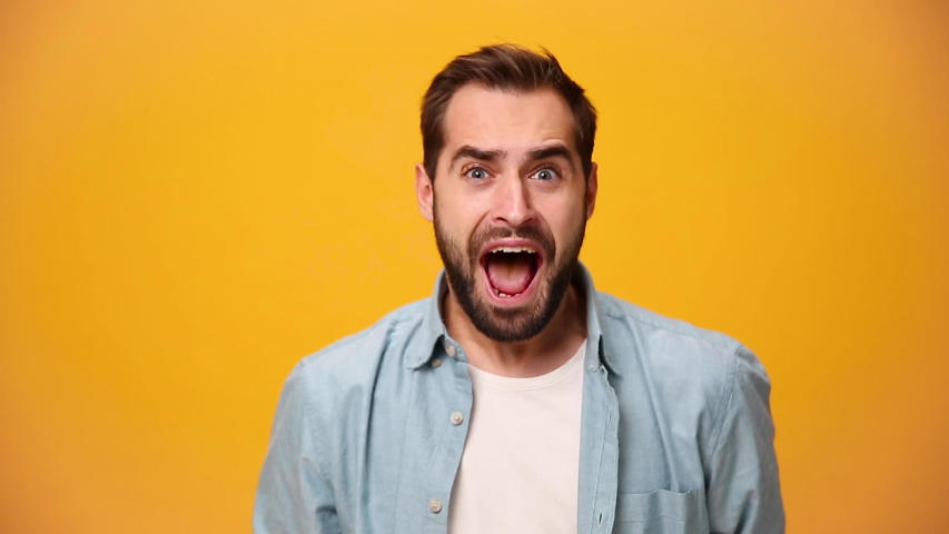 Handsome unshaven bearded young guy 20s in denim shirt white t-shirt isolated over yellow background in studio. People sincere emotion lifestyle concept. Looking at the camera scream win enjoy delight | Shutterstock HD Video #1042986751