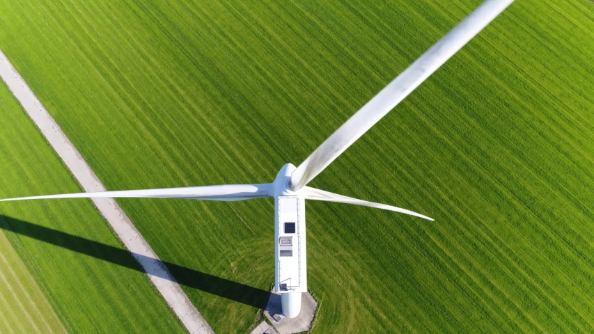 Aerial footage of wind turbine providing sustainable energy by spinning blades the power also known as renewable is collected from resources green field meadow in background 4k high resolution Royalty-Free Stock Footage #1042994104