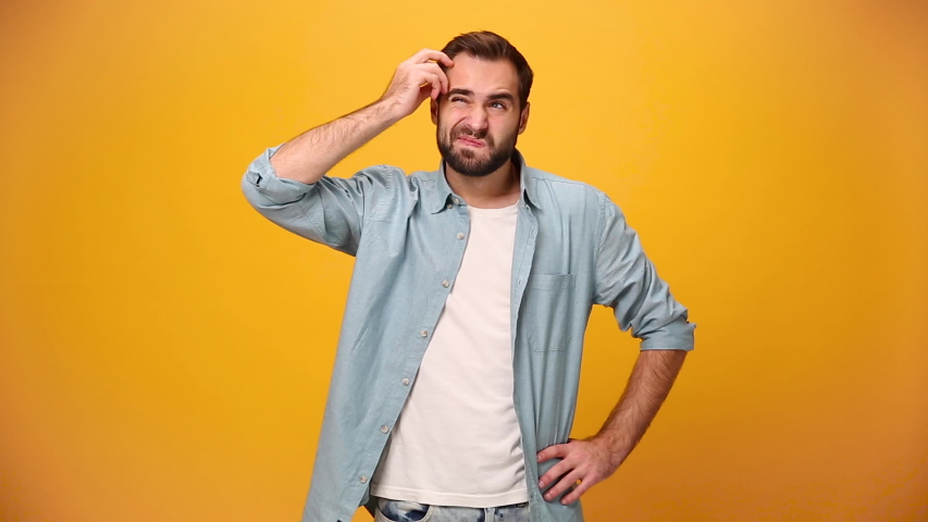 Bearded young guy 20s in denim shirt white t-shirt isolated on yellow background in studio. People sincere emotions, lifestyle concept. Looks at camera, thinks, scratches at temple comes up with ideas   Shutterstock HD Video #1042994944