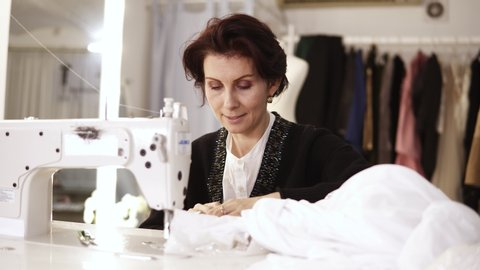 Portrait of an adult woman seamstress works at a sewing machine, working on a white hand made dress. Fashion clothes on the background in tailor's studio. Woman working on a wedding dress