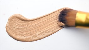 Foundation face make-up smudge, smear. Cosmetic liquid foundation or bb cream beige color smudge, smear, stroke. Make up smears isolated on a white background. Brush. Texture. 4K UHD video
