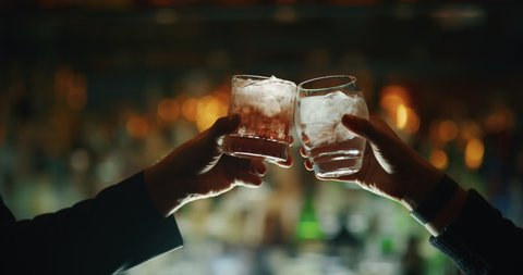 Close up of two people are cheering with cocktails in a bar or disco club.
