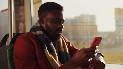 Attractive african young businessman wearing autumn outfit using a smartphone device driving in public transport admiring bright sunrise behind a window.