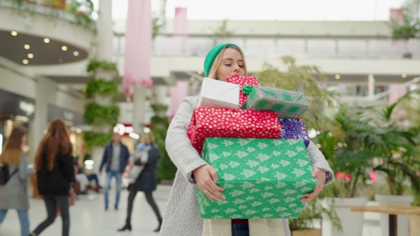 Young attractive woman in hurry carrying a pile of colorful Christmas presents at shopping mall. Blonde girl in coat shopping gifts for family before boxing day. Consumerism.