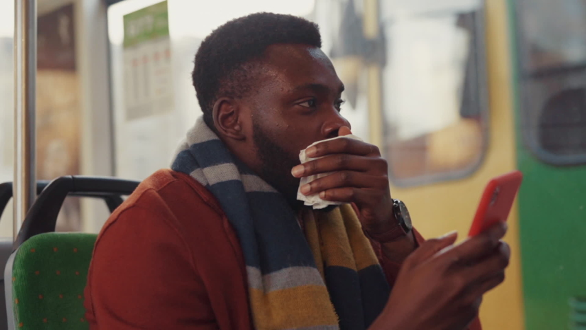 Unhealthy business black man suffering allergy sneezing and coughing in paper napkin sitting in public tram driving to work of fall morning. Concept of sickness. | Shutterstock HD Video #1043003530