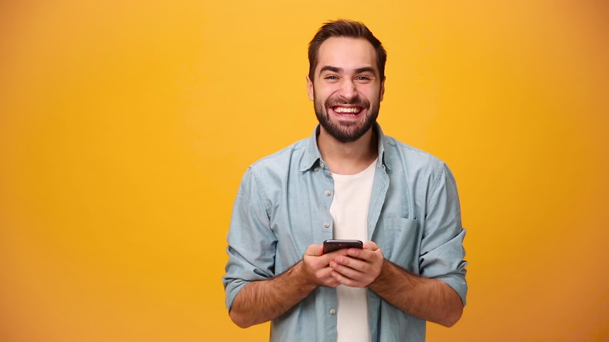 Handsome unshaven bearded young guy 20s in denim shirt white t-shirt isolated on yellow background in studio. People sincere emotions, lifestyle concept. Looking surprised wow, using mobile cell phone