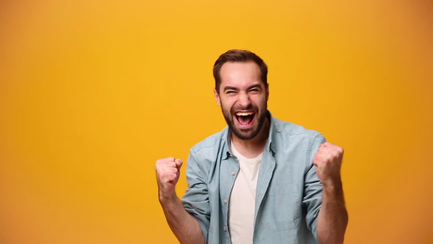Handsome bearded young guy 20s in denim shirt white t-shirt isolated over yellow background in studio. People sincere emotions, lifestyle concept. Looking at the camera doing winner gesture, say yeah