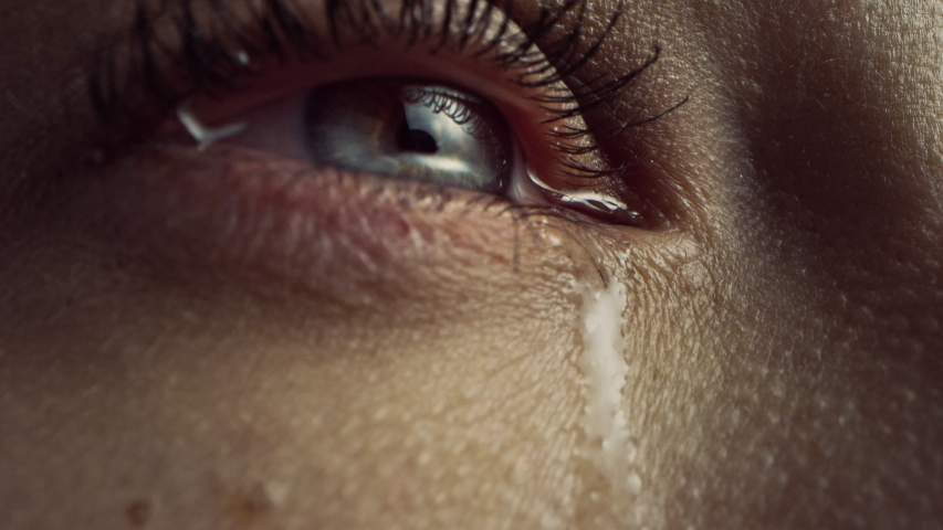 Close Up Macro Zoom Shot of a Crying Eye. Young Beatiful Female with Natural Light Blue, Yellow and Brown Color Pigmentation on the Iris. Mascara is Applied to Eyelashes. Tears are Flowing Down. | Shutterstock HD Video #1043006284