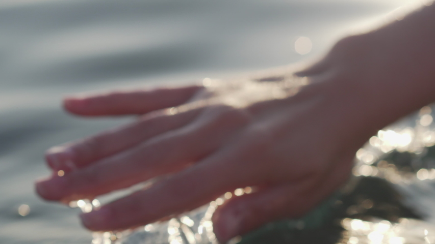 Female hand playfully and gently touches the sea surface in the glare of the sun at sunset, Close-up, | Shutterstock HD Video #1043006431