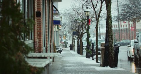 Street with Christmas Decoration and Snow falling in Slo Motion