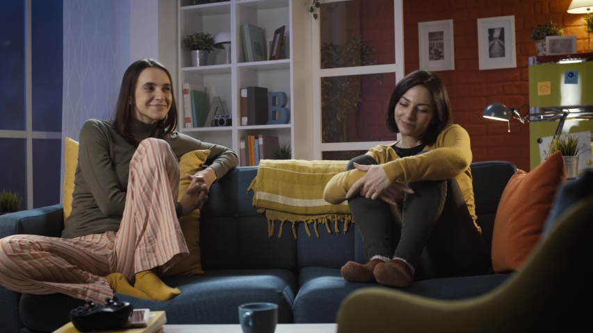 Cheerful young friends at home, they are sitting on the sofa and eating pizza together: lifestyle and food concept | Shutterstock HD Video #1043018188
