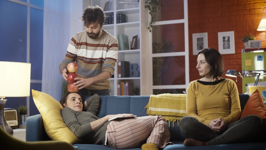 Friends spending time together at home: a man is stacking and balancing apples on his friend's head and another girl is watching them and smiling   Shutterstock HD Video #1043018227