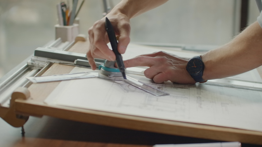 Architect's desk: drawings, tape measure, ruler and other drawing tools. Engineer works with drawings in a bright office, close-up. Insturments and office for designer. Male hands draw with a pencil | Shutterstock HD Video #1043036374