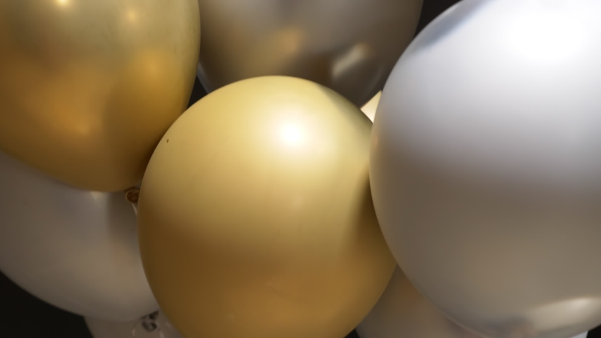 A lot of balloons of gold and silver soar on black background. | Shutterstock HD Video #1043038639