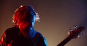 An amazing rock music player performing. Grunge musician is playing rock on bass guitar on stage, making a cool solo in red and blue neon lights 4k footage