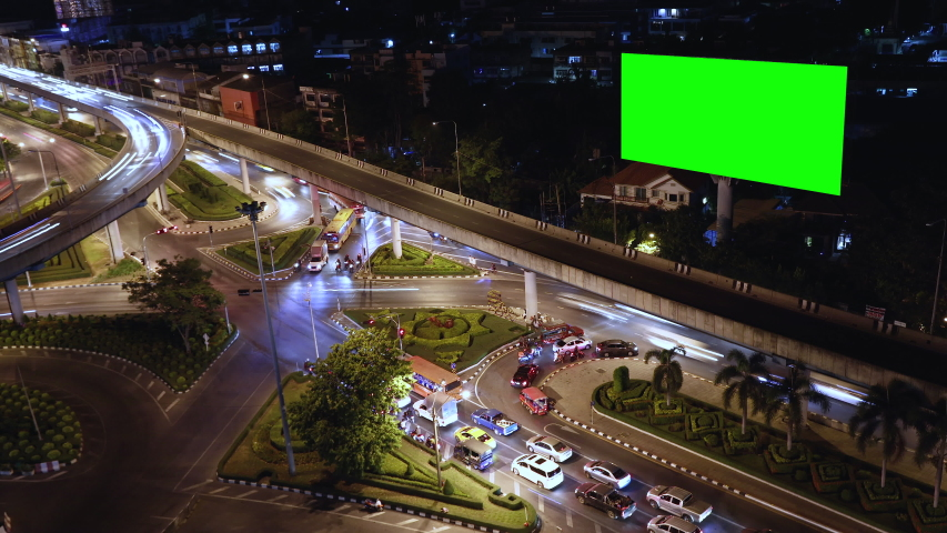 4k - Advertising billboard green screen on sidelines of expressway with traffic at evening, time lapse.