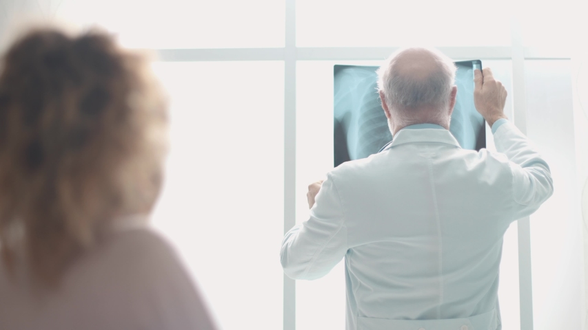 Professional doctor giving a consultation to a patient in wheelchair, he is checking a radiography and smiling to the woman | Shutterstock HD Video #1043063758