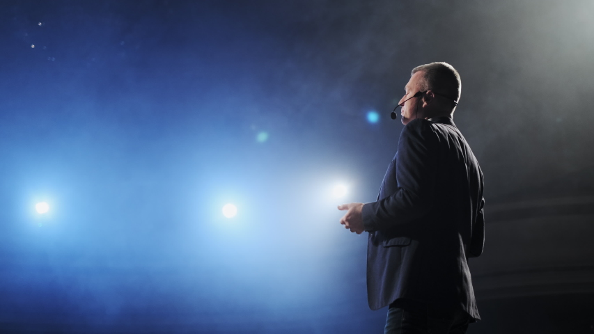 Rear view of men speaking through a microphone in dark conference hall. Man talks into microphones at press conference. Profile of mature male politician speaking passionately from tribune Royalty-Free Stock Footage #1043066377