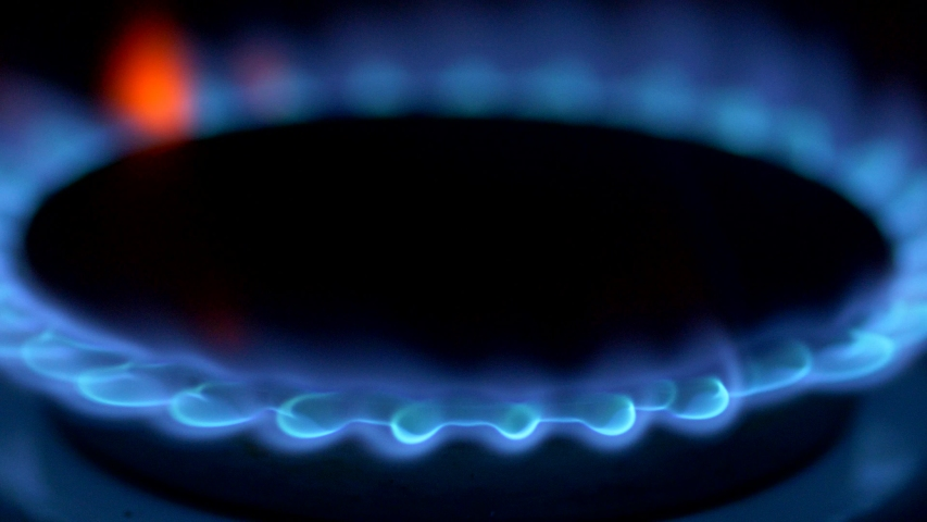 Methane firing up with blue flame on gas stove burner in total dark room. 4K
