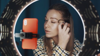 Pretty female beauty blogger sits in front of ring light and orange smartphone, doing contouring on her face, showing technique of makeup, recording tutorial beauty video. Shot on 4K RED camera.