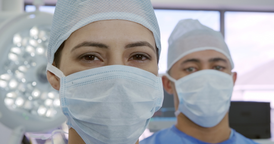 Front view close up of a mixed race female and a mixed race male healthcare professional wearing a surgical caps and masks in a hospital. Healthcare workers in the Coronavirus Covid19 pandemic #1043121724