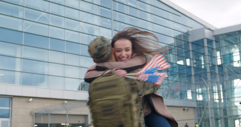 Happy wife with american flags running to her husband in military uniform. Excited soldier meeting, hugging and cuddling his girlfriend near airport. Concept of military retirement