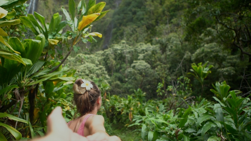 Young couple holding hands woman leading boyfriends walking through stunning lush green jungle. Follow me to concept.  | Shutterstock HD Video #1043128948