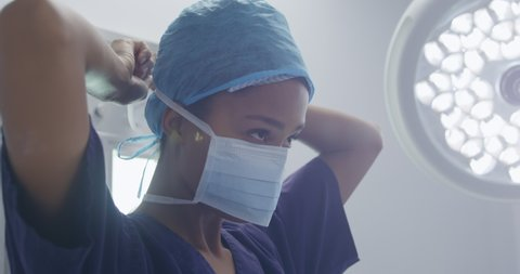 Side view close up of a Caucasian female healthcare worker in a hospital, wearing a surgical cap and putting on a surgical mask. Healthcare workers in the Coronavirus Covid19 pandemic
