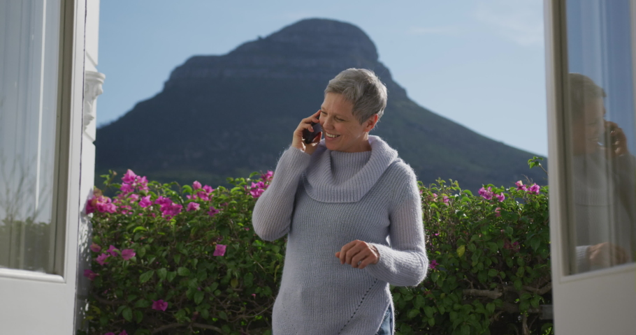 Front view of a senior Caucasian woman with short grey hair at home, standing in her garden wearing a cowl neck sweater talking on a smartphone, seen from the open doorway of her house, with flowers