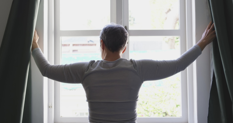 Rear view of a senior Caucasian woman with short hair standing and drawing the curtains at home, silhouetted against the window, slow motion,social distancing and self isolation in quarantine lockdown