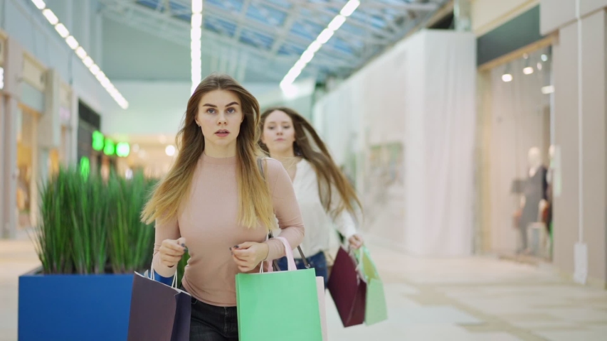 Two shopaholic young women with shopping bags running in slow motion along mall hurrying to make purchases on Black Friday. Woman pushing off her rival to be first in store