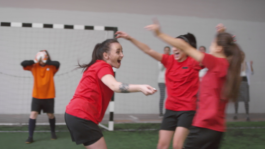 Group of young joyous female players jumping, huddling and giving high five to each other while celebrating soccer goal during match on indoor sports field