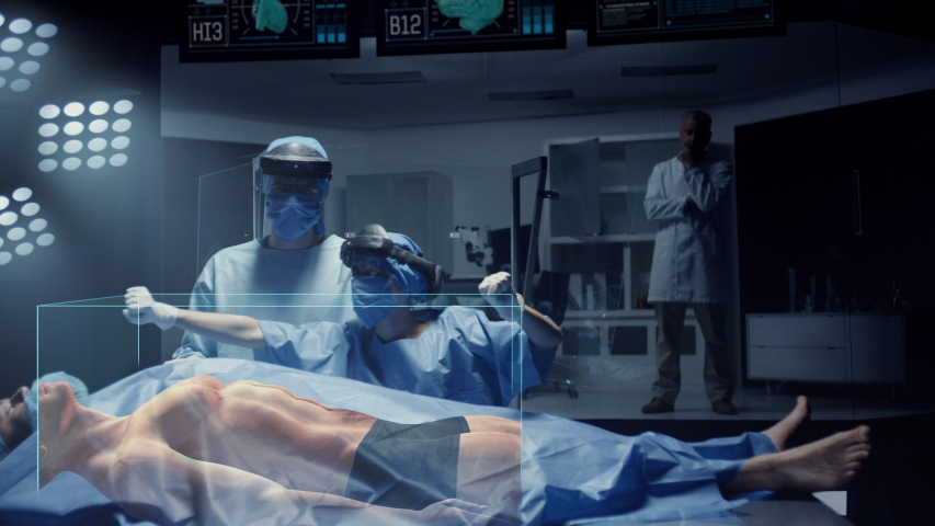 Team of Medical Surgeons use Augmented Holographic Technology to examine Patient. Nurse uses Hand Gestures to show the Organs, Bones and Full Anatomy of the Body of a Male Patient. Shot on RED Epic W. Royalty-Free Stock Footage #1043173177