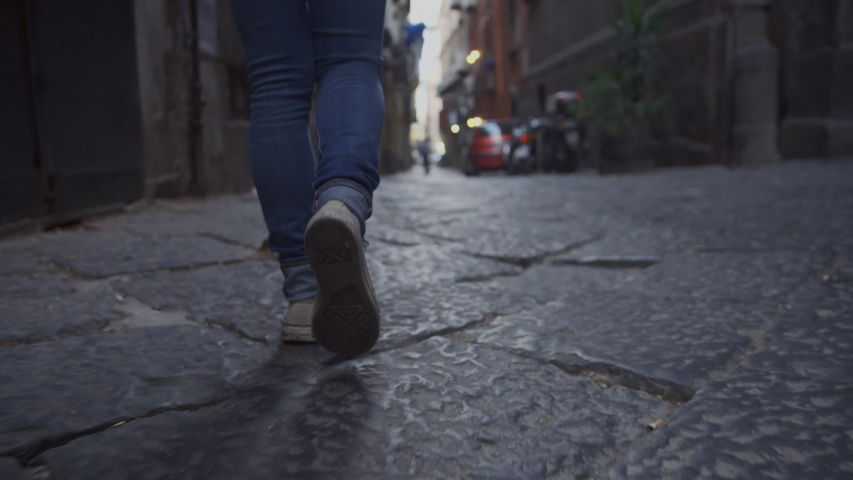 Low-angle handheld shot of a youthful woman walking down a dark old abandoned alleyway at dusk. Ground view of a woman's feet as she walks along a cobblestone path in Naples, Italy. Slow Motion, 4K. | Shutterstock HD Video #1043184148