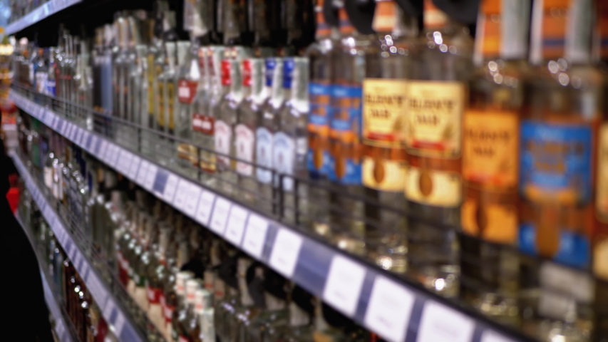 Alcohol Sale in Supermarket in Blur. Rows and Shelves of Bottled Alcohol in a Store Window. Buyers Choose Alcoholic Beverages. Wine and Vodka Department. Customers select goods. Choose vodka in the | Shutterstock HD Video #1043186194